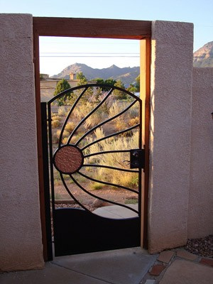 Arched top gate with Copper windblown sun design and solid wave panel on bottom