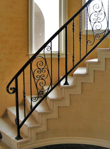 Curved stairway rail with custom Forged Scrolls and pickets