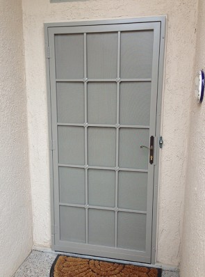 "Security door with Slimline lock, 3/4"" divided light with Cross Strap design and perforated metal"