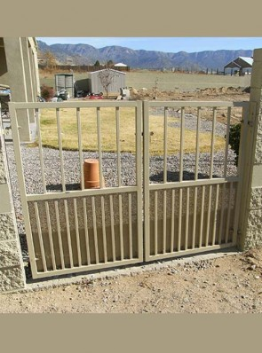 Double gates with doggie pickets and perforated metal on bottom