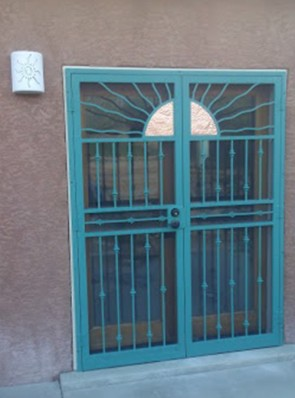 Pair of security pre hung screen doors in split wavy copper and sun on the top with knuckles design