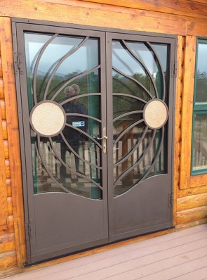 Pair of security storm doors with wind blown copper sun design