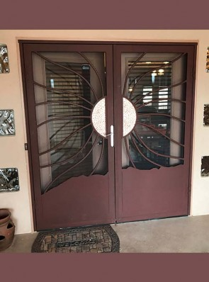 Pair of security storm doors with split wavy copper sun and mountain bottom panel