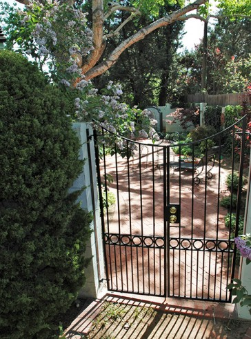 Pair of gates with reversed arched circles and doggy pickets