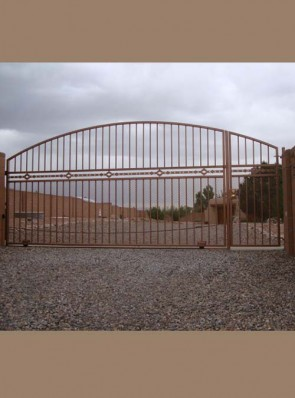 Arched sliding automatic gate with High Desert design and expanded metal on bottom