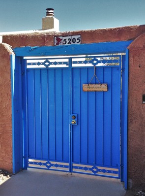 Double courtyard gates with high desert design and solid metal on back