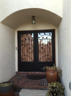 Pair of security storm doors in large scroll design with leaves and kick panel