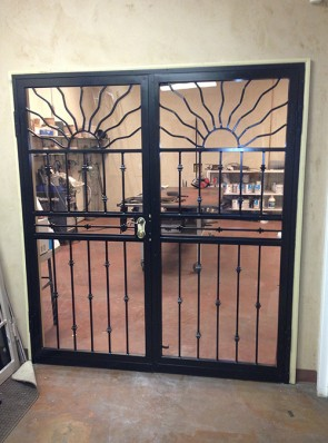Pair of security storm doors with wavy sun on top and knuckles design